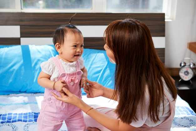Mutter spricht mit weinendem baby