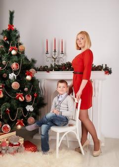 Mutter steht und jungen auf einem weißen stuhl sitzen