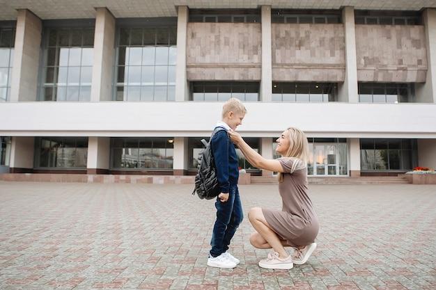 Mutter streichelt ihren sohn und begleitet ihn zur schule.