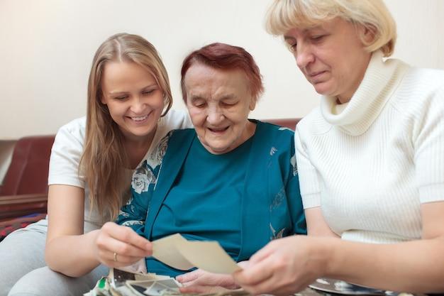 Mutter, tochter und großmutter, die fotos betrachten