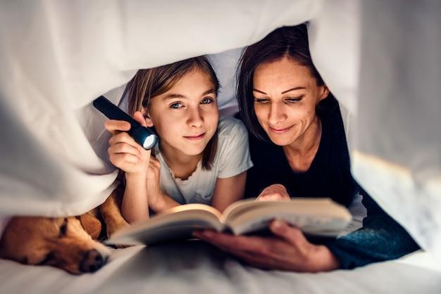 Mutter, tochter und hund, die spät in der nacht auf das bett und das lesebuch legen
