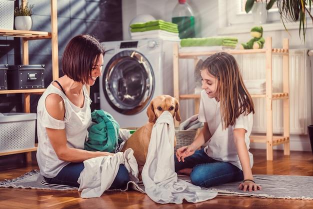 Mutter, tochter und hund, die spaß an der waschküche haben