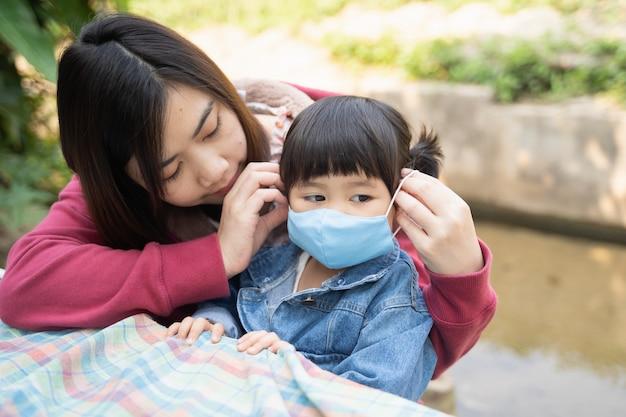 Mutter trägt eine maske für ihre kinder, schützt covid-19-coronavirus im café