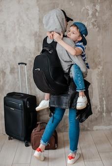 Mutter trägt einen kleinen sohn auf einem koffer im wartezimmer des transports.