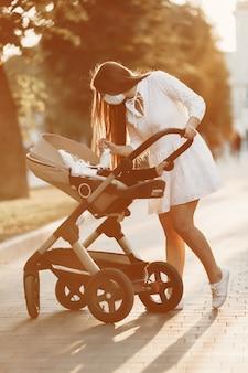 Mutter trägt gesichtsmaske. frau, die baby im kinderwagen geht. mutter mit kinderwagen während der pandemie, die einen spaziergang im freien macht