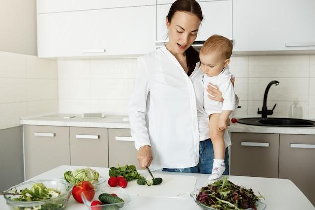 Mutter tragen baby und bereiten gesundes essen zu, hacken gemüse