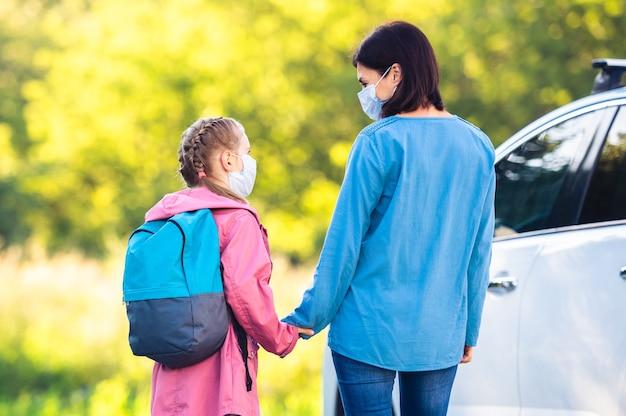 Mutter trifft tochter nach der schule während der pandemie neben dem auto am sonnigen tag