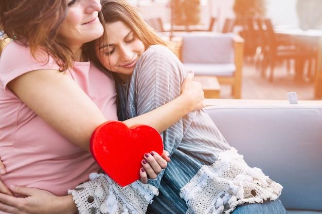 Mutter umarmt frau für gegenwart