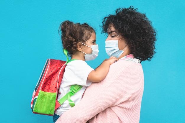 Mutter umarmt ihre tochter, die zurück zur schule geht - familienangehörige, die gesichtsmasken tragen - vorschule während des coronavirus-ausbruchskonzepts - hauptaugenmerk auf muttergesicht