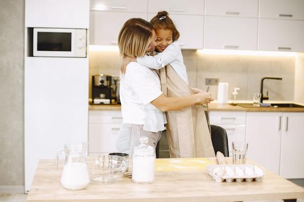 Mutter umarmt ihre tochter. fürsorgliche glückliche mutter, die zusammen mit kleinem ethnischem kind kocht