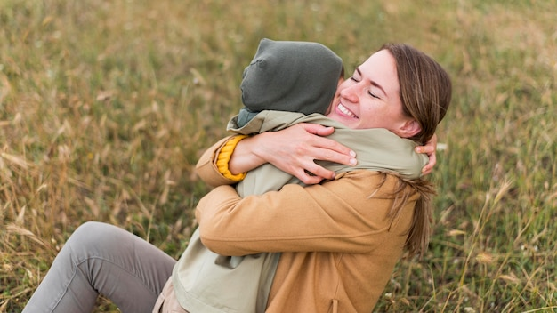 Mutter umarmt ihren sohn, während sie auf gras sitzt