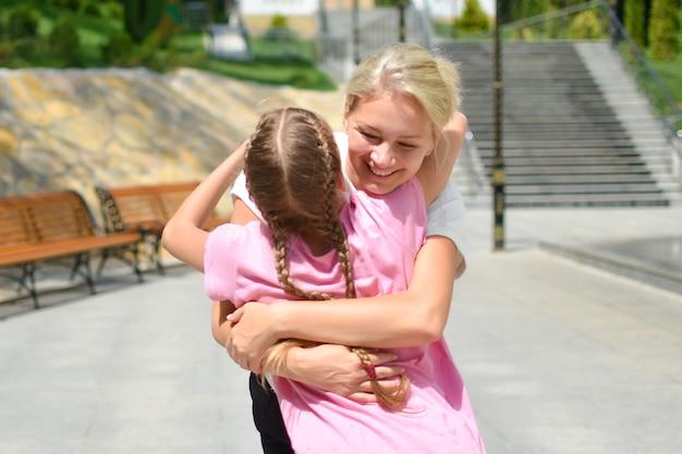 Mutter umarmt jugendlich tochter, glückliche familie