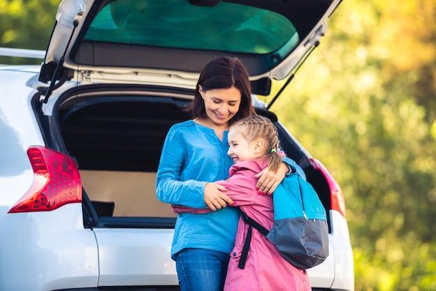 Mutter umarmt kleines mädchen nach der schule neben dem offenen kofferraum
