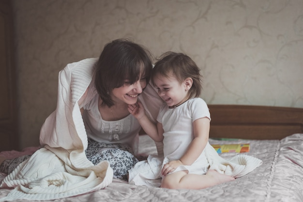 Mutter umarmt und spielt mit ihrer tochter verstecken im bett, lebensstil,