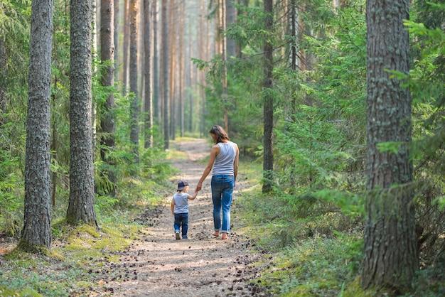 Mutter und baby gehen auf landstraße im kiefernwald