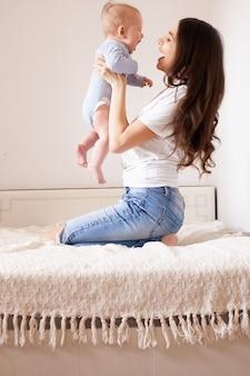 Mutter und baby im bett. junge mutter spielt mit ihrem neugeborenen sohn. kind und eltern zusammen zu hause. familie mit kindern am morgen. frau, die mit kind in einem sonnigen schlafzimmer entspannt. glück und mutterschaft