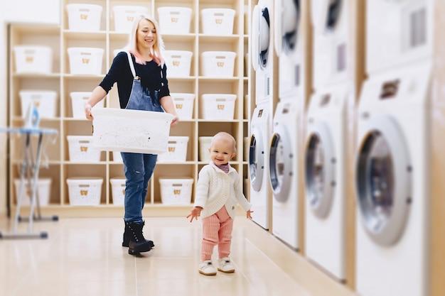 Mutter und baby in der wäscherei nehmen dinge und spielen