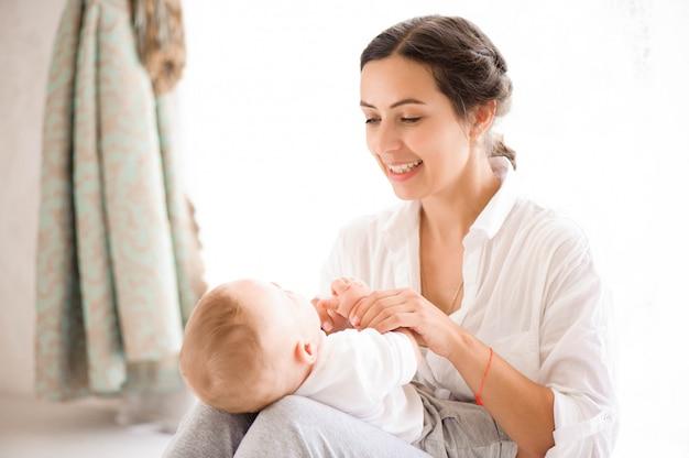 Mutter und baby in der windel, die im sonnigen schlafzimmer spielt. familienhavi