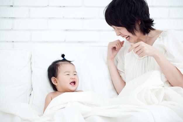 Mutter und baby lächeln sich auf einem weißen stuhl glücklich an.
