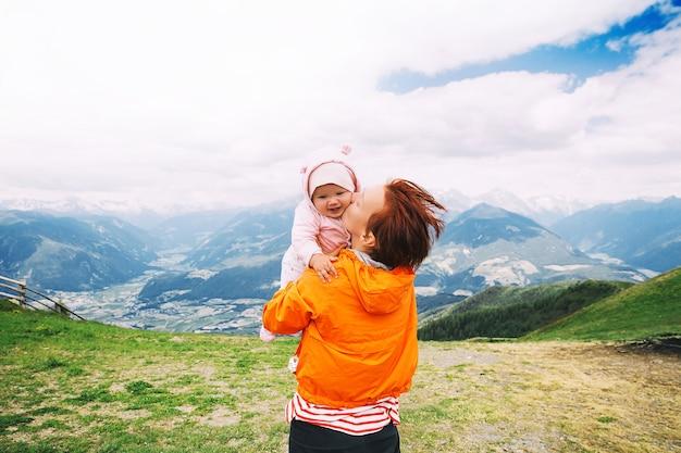 Mutter und baby mit bergen auf einem hintergrund. familie verbringen sommerferien in den dolomiten, italien, europa. blick auf bruneck und das pustertal vom gipfel des kronplatzes.