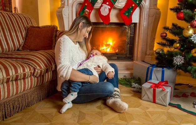 Mutter und baby sitzen auf dem boden am weihnachtlich dekorierten kamin