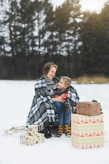 Mutter und baby sitzen auf holzschlitten im winterwald und trinken heißen tee