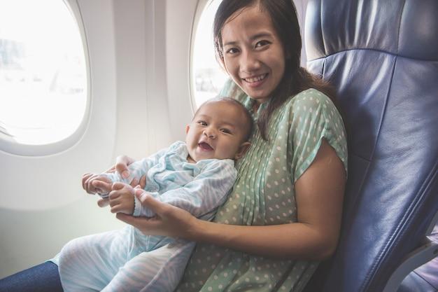 Mutter und baby sitzen zusammen im flugzeug