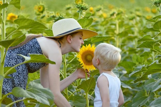Mutter und baby sohn stehen und atmen den duft der sonnenblume ein