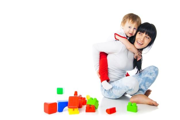 Mutter und baby spielen mit bausteinen spielzeug isoliert auf weiß