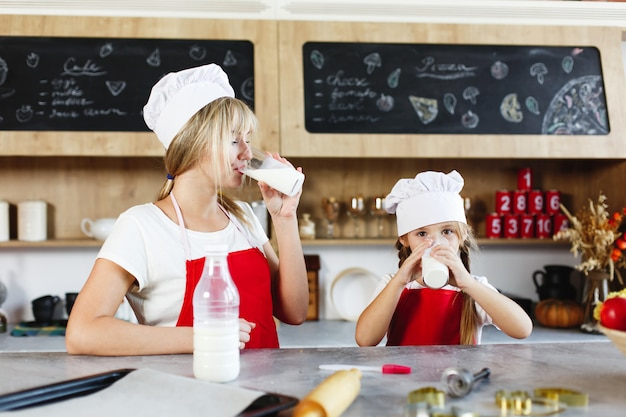 Mutter und charmante kleine tochter haben spaß beim trinken von milch am tisch in einer gemütlichen küche