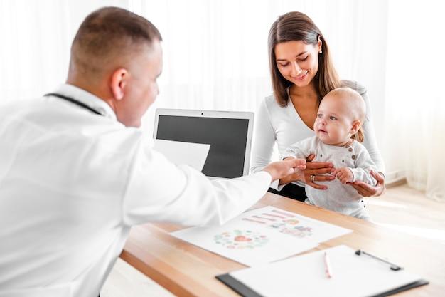 Mutter und doktor, die kleines baby betrachten