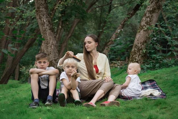 Mutter und drei kinder im park auf der lichtung. familienpicknick im freien.
