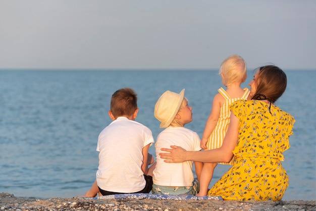 Mutter und drei kinder ruhen sich an der küste aus. große familie auf see. sommerferien.