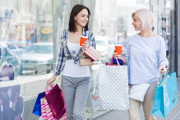 Mutter und erwachsene tochter, die zusammen kaufen tun. mittlere erwachsene mutter und ihre tochter im einkaufszentrum.