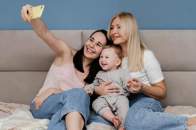 Mutter und großmutter machen selfie mit kind