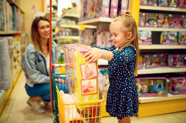 Mutter und hübsches kleines mädchen, das eine puppe im spielzeugladen kauft