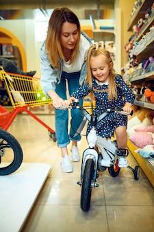 Mutter und hübsches kleines mädchen, das fahrrad im kinderladen wählt