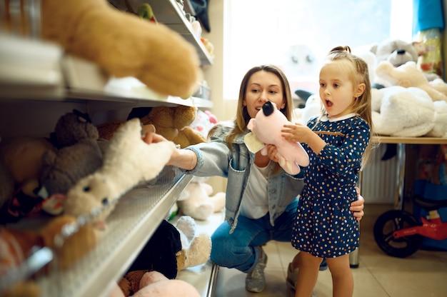 Mutter und hübsches kleines mädchen, das stofftiere im kindergeschäft wählt