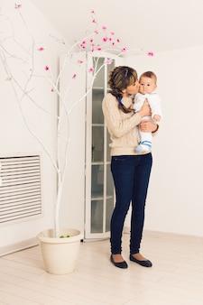 Mutter und ihr kind umarmen sich mit zärtlichkeit und sorgfalt und geben mutter blumen. muttertagskonzept, glück und liebe