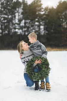 Mutter und ihr kleiner sohn gehen zusammen im winterwald und halten weihnachtskranz