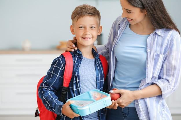 Mutter und ihr kleiner sohn mit brotdose vor der schule