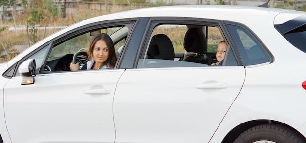 Mutter und ihr kleiner sohn warten in einem auto, das mit heruntergeklappten fenstern auf dem land geparkt ist, und mama späht ängstlich hinaus