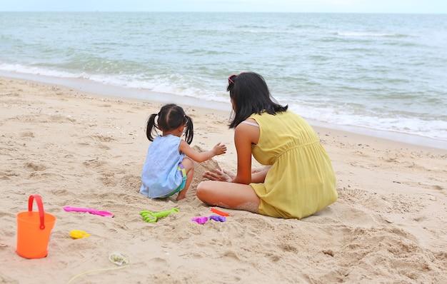 Mutter und ihr tochterkindermädchen, die sand mit dem tierblock sich bildet am strand spielen