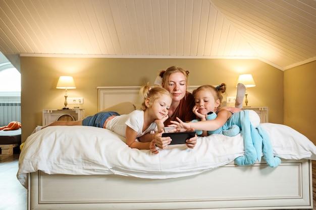 Mutter und ihre beiden kleinen töchter liegen auf dem bösen und schauen sich cartoons auf dem smartphone an oder spielen zusammen.