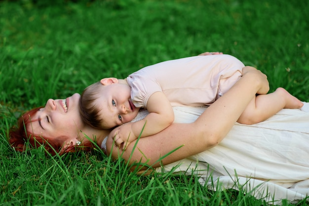 Mutter und ihre einjährige tochter umarmen sich im gras im park.