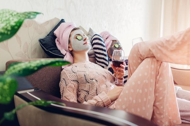 Mutter und ihre erwachsene tochter trugen gesichtsmasken und gurken auf die augen. frauen, die kühlen, während sie wein trinken