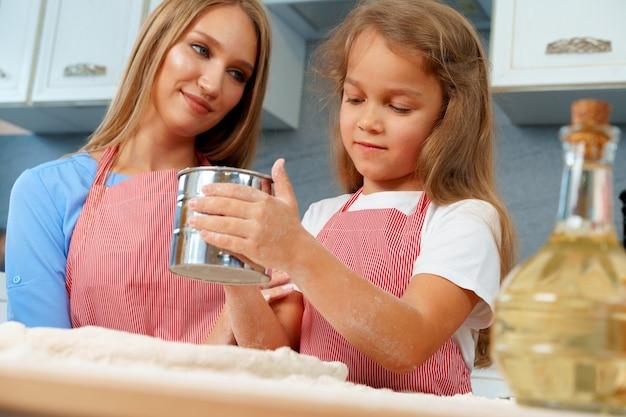 Mutter und ihre kleine tochter bereiten teig in der küche vor