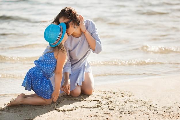 Mutter und ihre kleine tochter, die spaß an der küste haben. junge hübsche mutter und ihr kind, die nahe dem wasser spielt und herz auf dem sand zeichnet