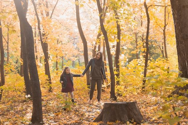 Mutter und ihre kleine tochter im herbstpark in der herbstsaison