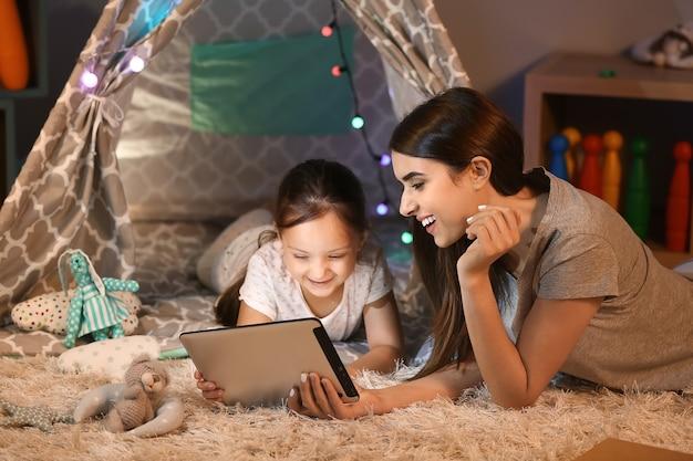 Mutter und ihre kleine tochter mit tablet-computer zu hause am abend